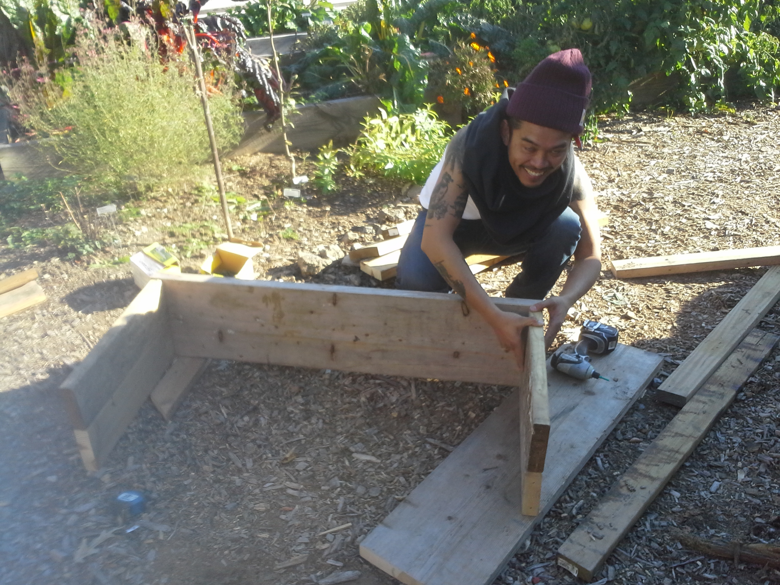 A friend making a compost bin out of my scrap lumber